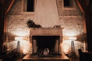 "A fire burns in a beautiful old fireplace decorated with the initials ""U and V"" on the mantle above."