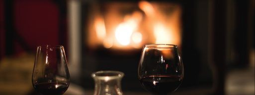 Two glasses of red wine sit on either side of a decanter on a table in front of a glowing electric fireplace.