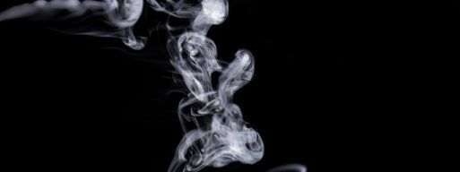 Grey smoke floats across a black background.