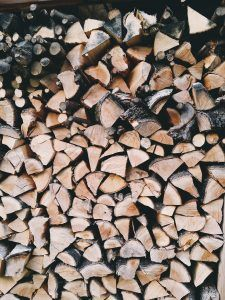 A stack of dried and seasoned firewood, ready for use in a wood burning fireplace.