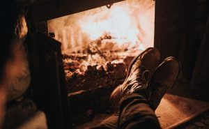 Man enjoys a warm wood burning fireplace