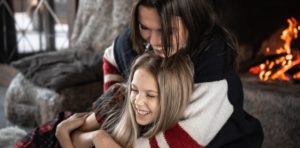 Mother hugs her daughter as they lie near the fireplace