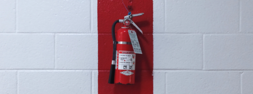 red fire extinguisher hanging on a white concrete wall